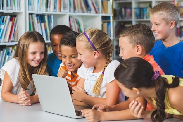 Школьники используют ноутбук в библиотеке