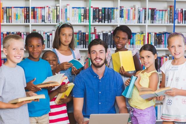 Учитель учит детей на ноутбуке в библиотеке