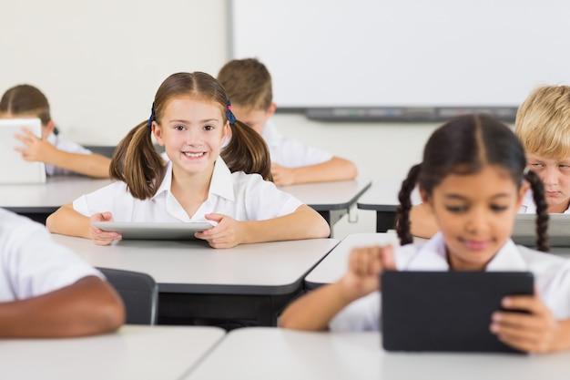 Школьница с помощью цифрового планшета в классе