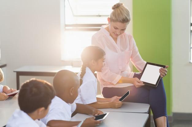Учитель обучает детей на цифровом планшете