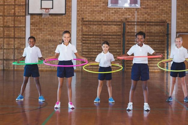 バスケットボールコートでフラフープで遊ぶ学校の子供たち