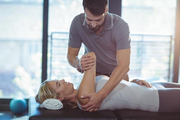 Физиотерапевт, проводящий терапию плеча женщине
