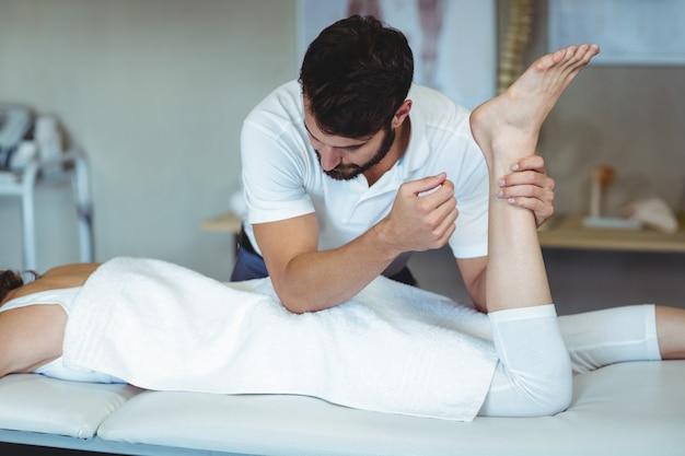 Физиотерапевт дает массаж бедра женщине