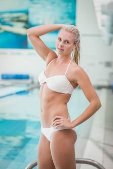 魅力的な女性はプールで水に入る