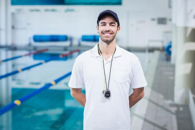 Красивый тренер, стоя с руки на спине в бассейне