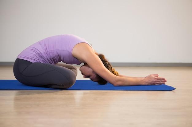 Женщина делает позу ребенка йоги на тренировочный мат