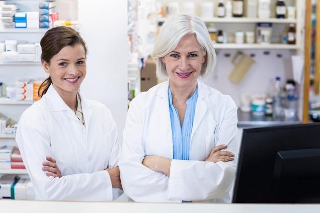 薬局で腕を組んで立っている笑顔の薬剤師