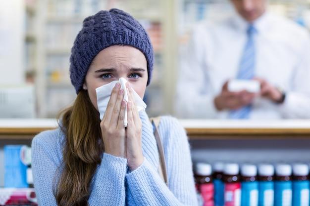 Клиент прикрывает нос, чихая в аптеке