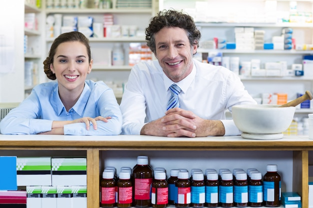 薬局のカウンターに寄りかかって笑顔の薬剤師