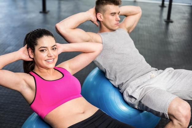ジムでフィットネスボールに腹部のクランチをしているフィットのカップル