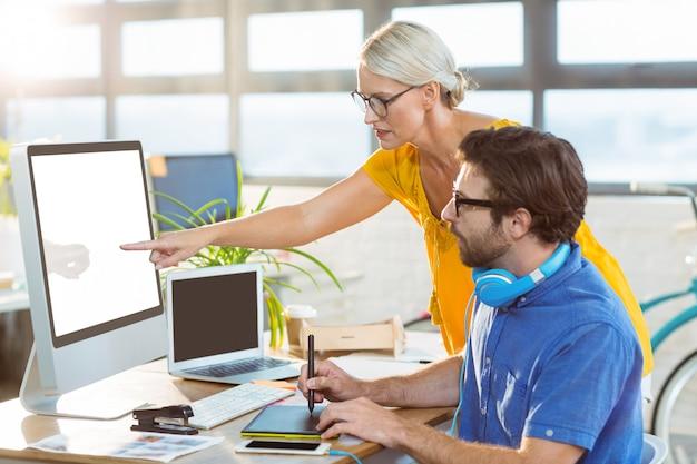 Графические дизайнеры, взаимодействующие во время работы на компьютере