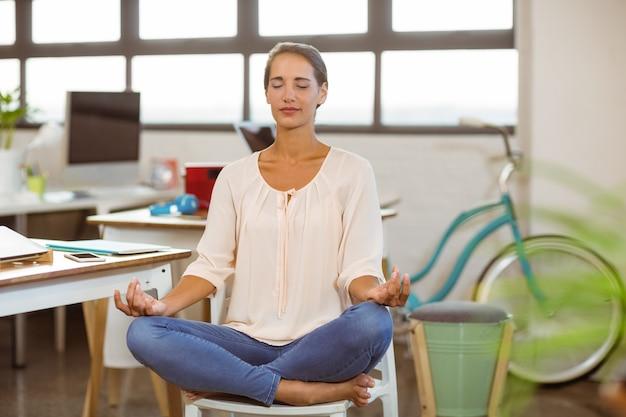 Женщина сидит на стуле и выполняет йогу