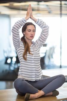 Женщина сидит на столе и выполняет йогу