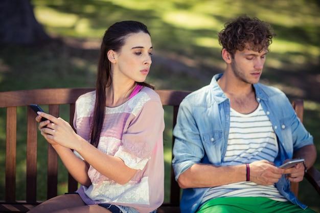 嫉妬深い女性が公園で彼女の男の携帯電話をスパイ