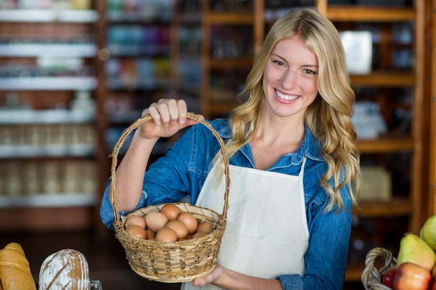 スーパーで卵のバスケットを持って笑顔の女性スタッフ