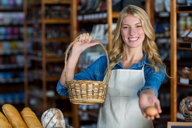スーパーマーケットでバスケットと卵を保持している女性スタッフの笑顔
