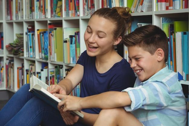 Школьники читают книги в библиотеке в школе