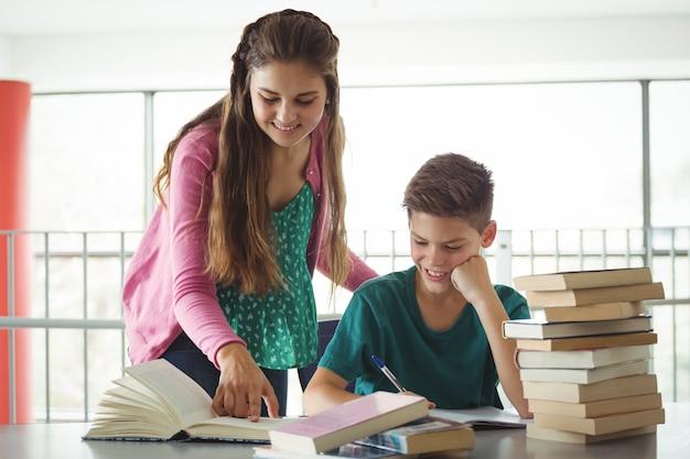 Школьники делают домашнее задание в библиотеке