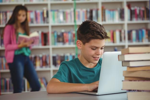 Школьник, используя ноутбук в библиотеке