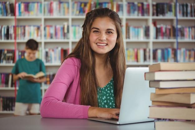Портрет счастливой школьницы, используя ноутбук в библиотеке