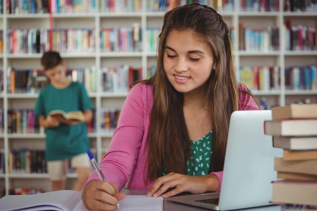 Школьница делает домашнее задание в библиотеке