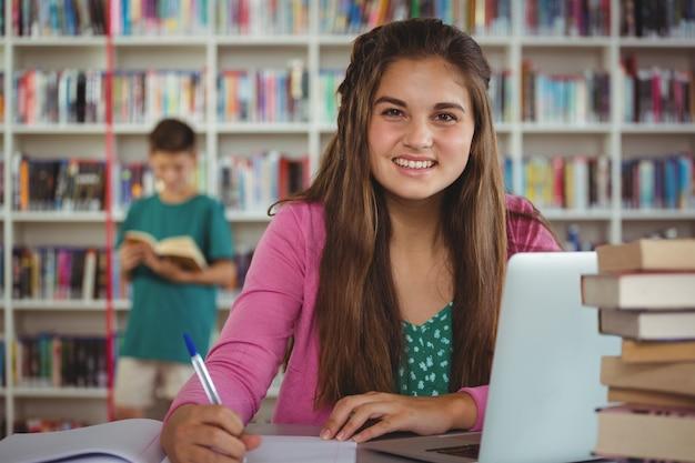 Школьница делает домашнее задание в библиотеке в школе