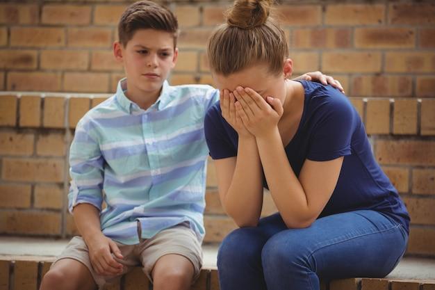 キャンパスのステップで彼女の悲しい友人を慰める少年
