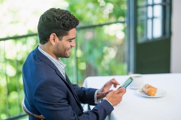 Улыбающийся бизнесмен с помощью мобильного телефона