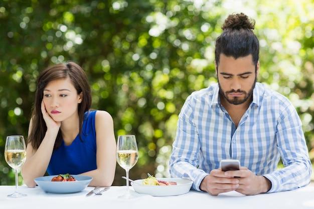 女性を無視して携帯電話を使用している男性