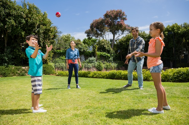 Счастливая семья играет с мячом в парке