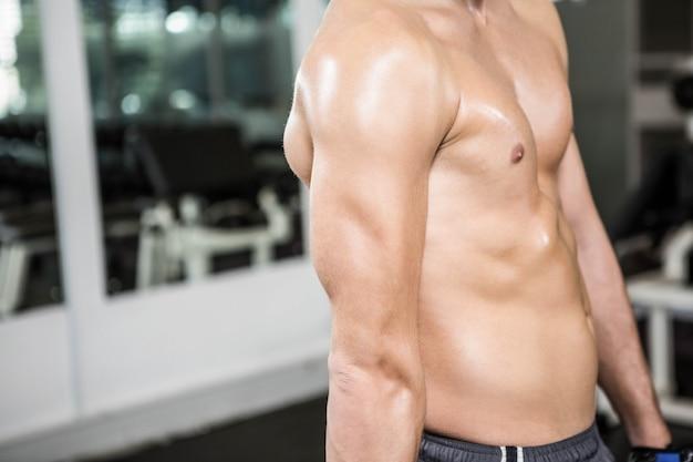 上半身裸の筋肉男、ジムで腕を示す