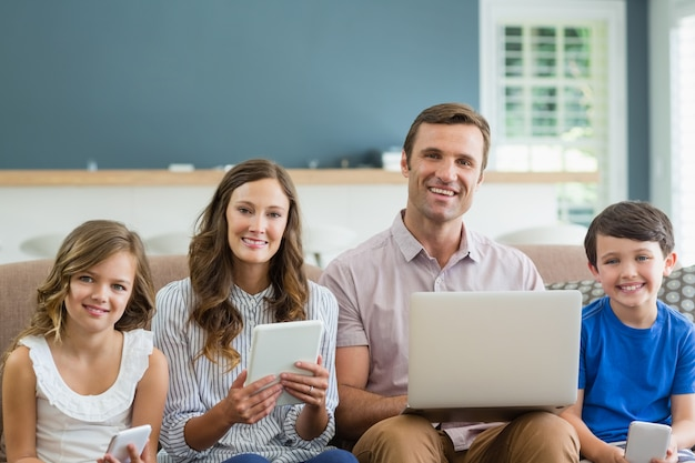 Улыбка семьи с помощью цифрового планшета, телефона и ноутбука в гостиной дома