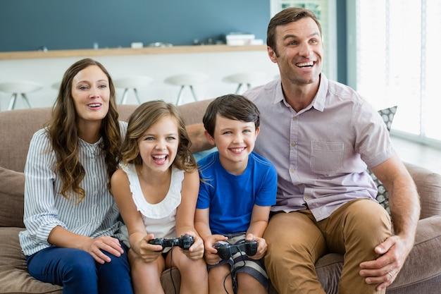 Счастливая семья, вместе играя в видеоигры в гостиной