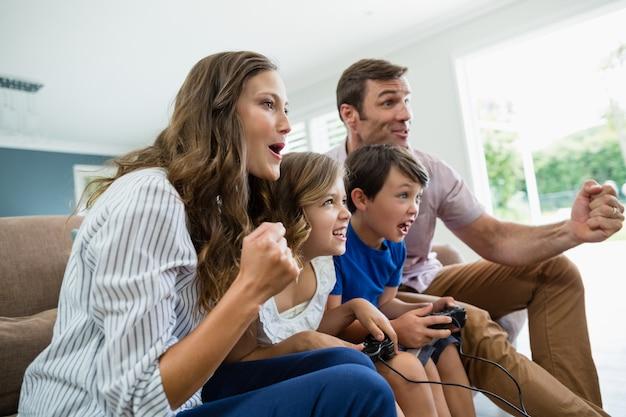 Возбужденная семья вместе играет в видеоигры в гостиной