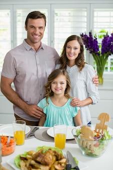 Портрет улыбающегося семьи обедают вместе на обеденном столе