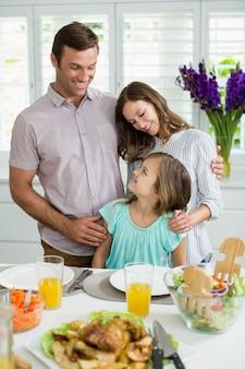 Улыбающиеся семьи общаются друг с другом во время обеда вместе