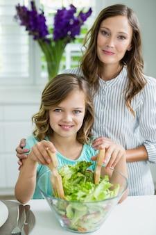 Портрет улыбается мать и дочь, смешивая миску салата на кухне