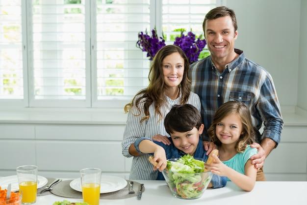 Портрет улыбающегося семьи готовит миску салата на кухне