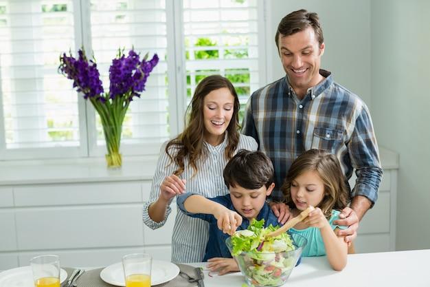 Улыбающиеся семьи готовит салат на кухне