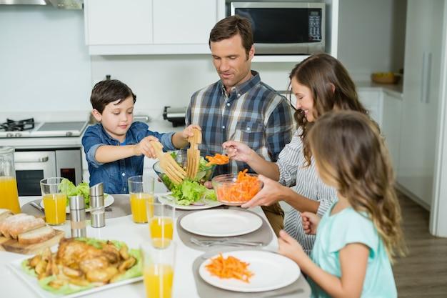 Улыбающаяся семья обедает вместе на обеденном столе
