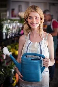 フラワーショップで水まき缶を保持している女性の花屋の笑顔