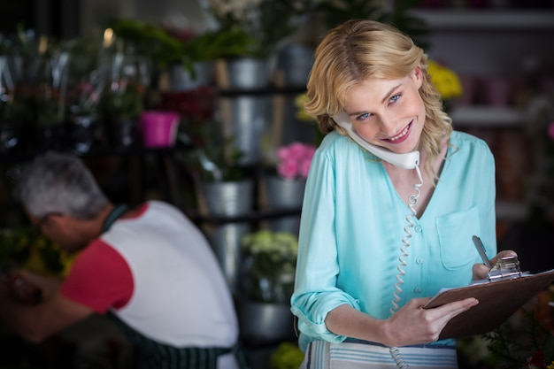 電話で注文する笑顔の女性花屋