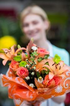 Женский флорист держит букет цветов