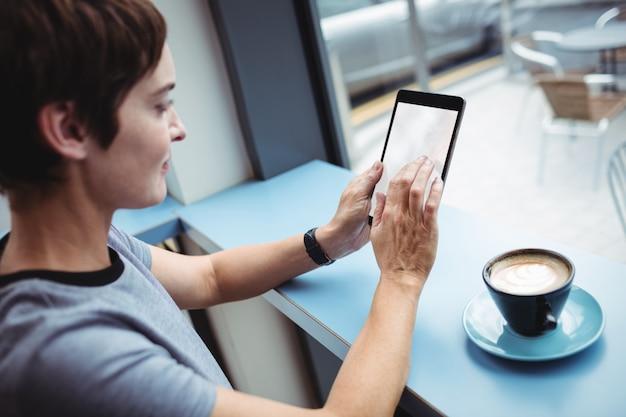 コーヒーを飲みながらデジタルタブレットを使用して実業家
