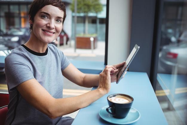 オフィスでコーヒーを飲みながらデジタルタブレットを使用して実業家