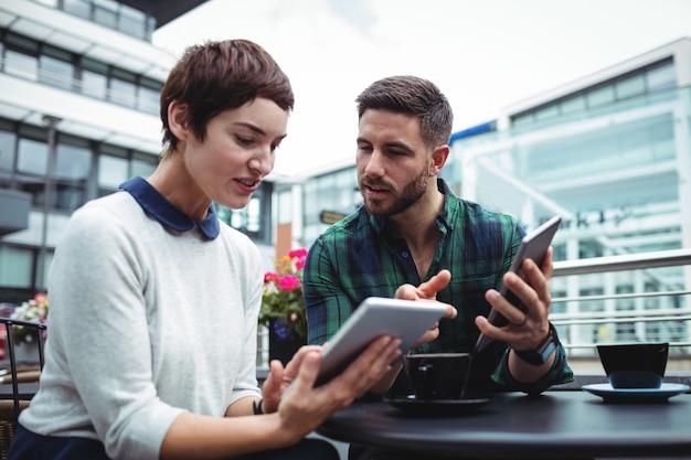 コーヒーを飲みながらデジタルタブレットに関するビジネスマンの議論
