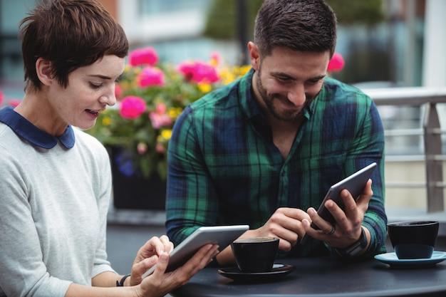コーヒーを飲みながらデジタルタブレットを使用するビジネスマン