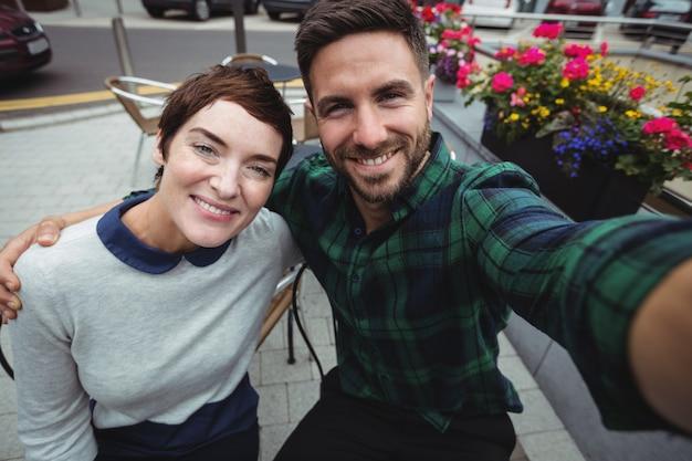 カフェテリアで自分撮りのためにポーズのカップル