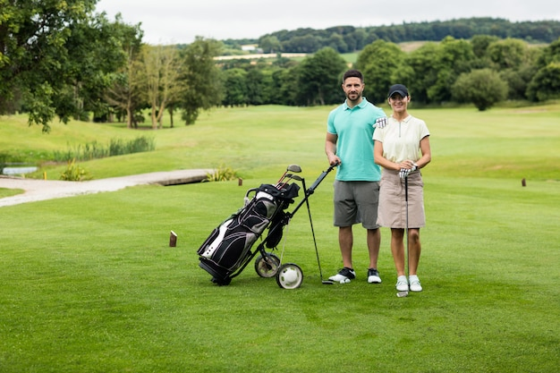 ゴルフクラブとゴルフコースでバッグと立っているカップル