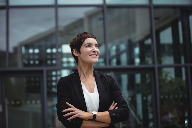 事務所ビルに立っている笑顔の実業家